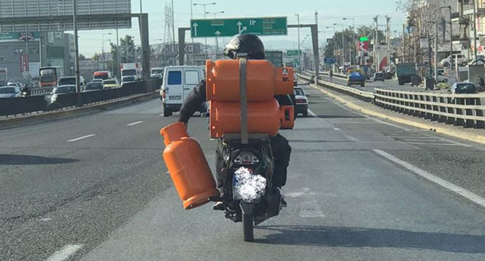 Ελλάδα 2020: Άντρας μεταφέρει τρεις φιάλες γκαζιού με το μηχανάκι του